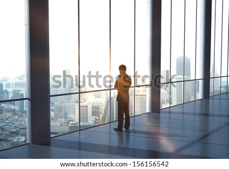 man thinking and standing in office - stock photo