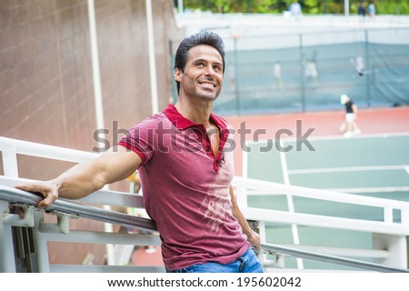 Man thinking of you. Wearing a red Polo shirt, blue jeans, stretching arms on the railing, a handsome, sexy, middle age guy is standing by a tennis court, looking up, smiling, thinking.