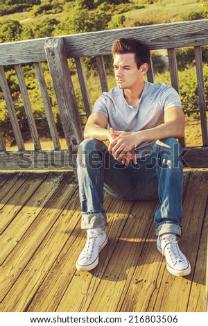 Man Thinking Outside. Wearing a gray T shirt, jeans, white sneakers, a young handsome guy is sitting on the wooden floor,  back against fence in a remote location, relaxing, thinking, lost in thought. - stock photo