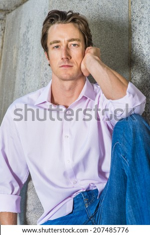 Man Thinking Outside. Wearing a light pink, long sleeve shirt, blue jeans, a young handsome guy is casually sitting against a concrete wall, thinking  - stock photo