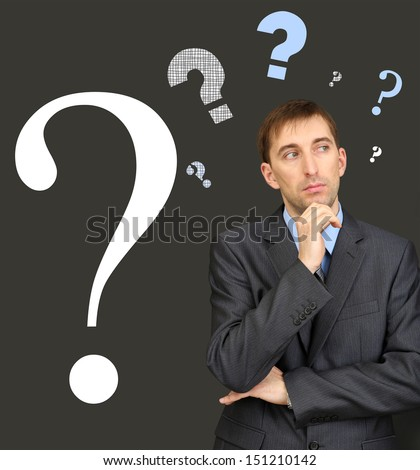 Man thinking surrounded by question on dark background