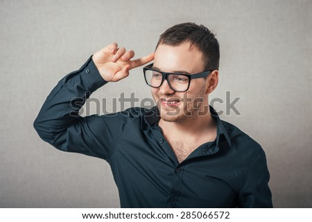 Man thinks upset with his hand near his head. On a gray background.