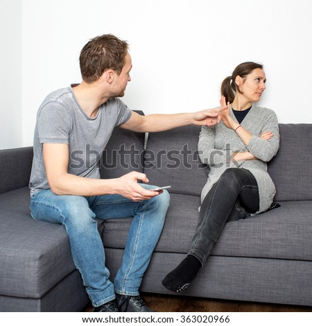 Man threatening woman which reacts calm - stock photo