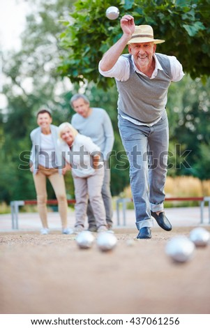 Man throwing ball while playing boule outside in a city - stock photo