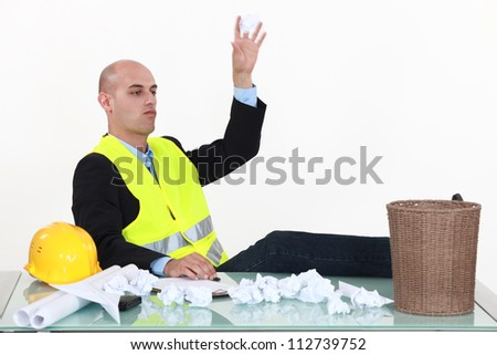 Man throwing papers in trash can - stock photo