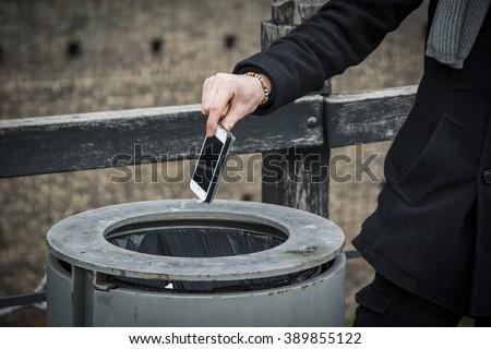 Man throwing phone in garbage bin - stock photo