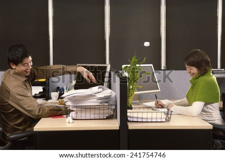 Man throwing wad of paper at co-worker - stock photo