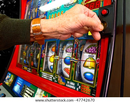 Man throws coin into a slot machine - stock photo