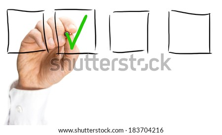 Man ticking a hand drawn check box in a line of four blank boxes on a virtual interface with a green check mark conceptual of success, yes or accepted, hand only on white with copyspace. - stock photo