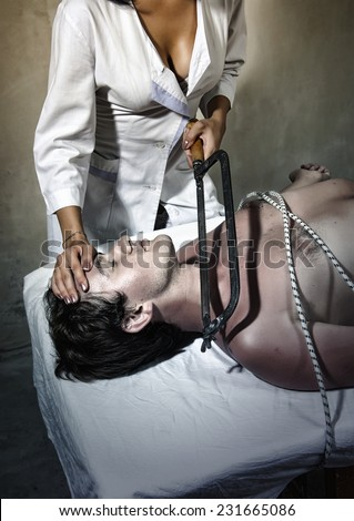 Man tied to a table and woman with a saw - stock photo