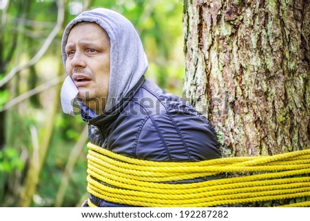Man tied to a tree in the forest - stock photo