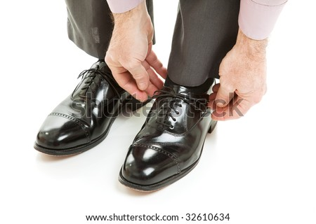 Man ties his shiney new black leather business shoes.  Isolated on white. - stock photo