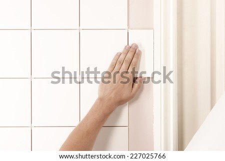 MAN TILING A WALL - stock photo