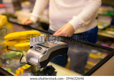 Man to pay at the checkout in the supermarket using credit card - stock photo