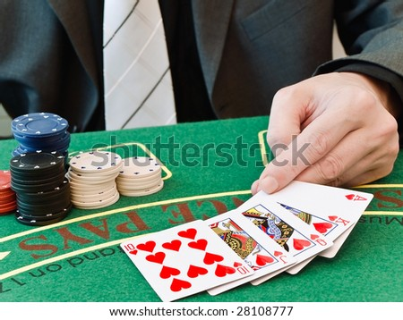 man to spread on the table a winning combination of poker - stock photo