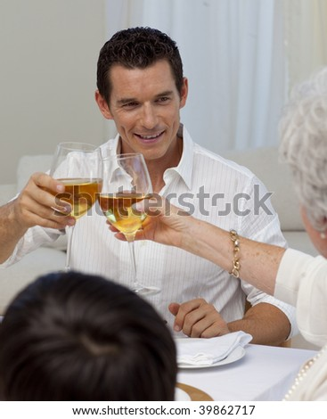 Man toasting with his mother in a Christmas dinner at home