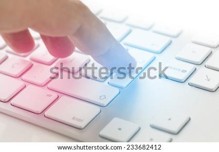 Man touching enter key on computer keyboard - stock photo