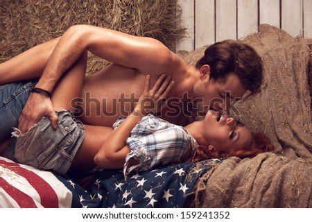 Man touching girl while kissing. Laying together on American flag  - stock photo