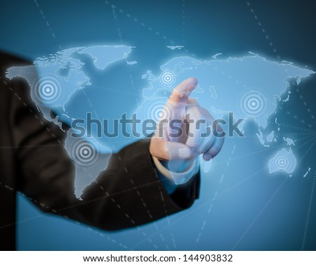 Man touching virtual world map by hand - stock photo