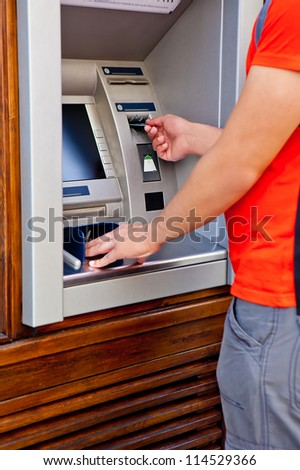 Man tourist at puts bank card into the ATM - stock photo
