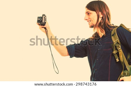 Man tourist backpacker on trip taking photo picture with camera. Young guy hiker backpacking. Summer vacation travel. Instagram filtered. - stock photo