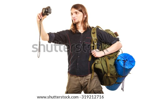 Man tourist backpacker on trip taking photo picture with camera. Young guy hiker backpacking. Summer vacation travel. Isolated on white background. - stock photo