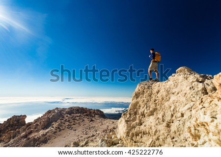 Man tourist hiker or trail runner looking at beautiful inspirational landscape in high mountains. Male runner with backpack, happiness and enjoying inspiring view on rocky top of mountain, Spain. - stock photo