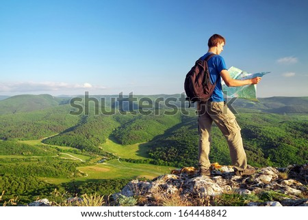 Man tourist in mountain read the map. Man on top of mountain. Tourism concept  - stock photo