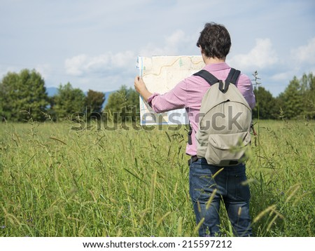 man tourist on a trip reading a map for the best way - stock photo