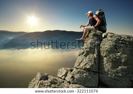 Man tourist on peak of mountain. Travel mountain scene. - stock photo