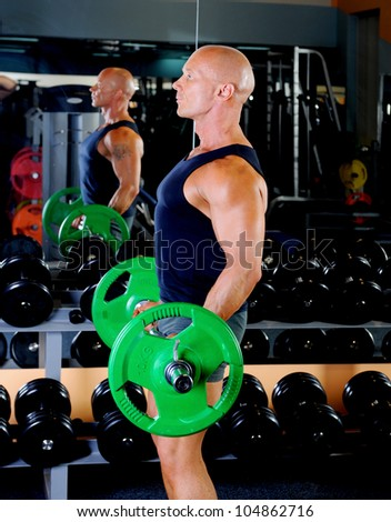 man trained in the gym does the rise of the bar for biceps - stock photo