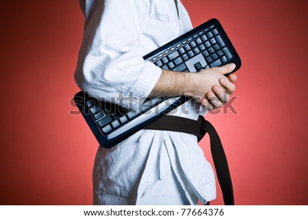 Man training karate with computer keyboard, sport and exercise concept