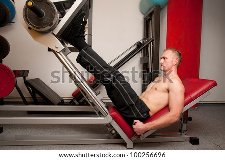 Man training leg muscles on a machine in fitness club