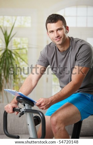 Man training on exercise bike at home, listening music. - stock photo