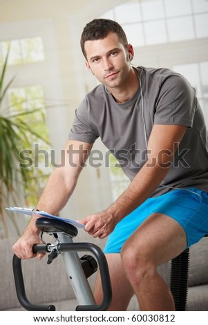 Man training on exercise bike at home, listening music.