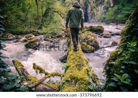 Man Traveler crossing river on log outdoor Lifestyle Travel survival concept  - stock photo