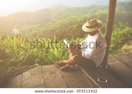 Man traveler is reading electronic book on portable touch pad, while is relaxing in the fresh air during trip in Asia.Male freelancer is working on digital tablet, while is sitting against jungle view - stock photo