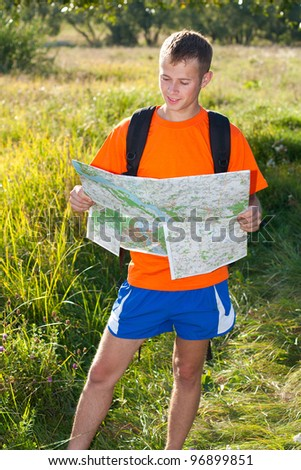 Man traveler read the map among the green summer's nature - stock photo