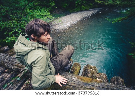 Man Traveler relaxing on wooden bridge over river Travel Lifestyle concept Summer journey vacations outdoor - stock photo
