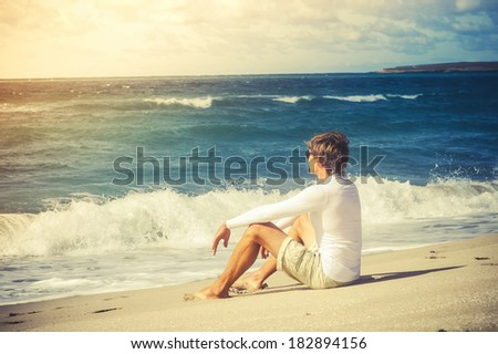 Man Traveler sitting on beach seaside looking on sea waves summer vacations Lifestyle concept - stock photo