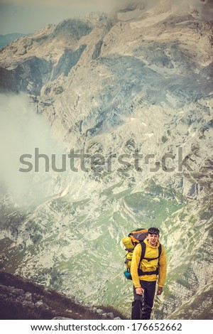 Man Traveler with Backpack hiking with Mountains on background - stock photo