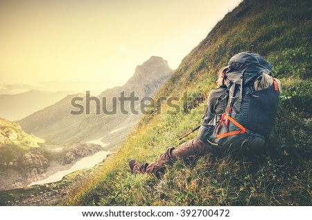 Man Traveler with big backpack relaxing Travel Lifestyle concept sunset mountains landscape on background Summer vacations adventure outdoor  - stock photo