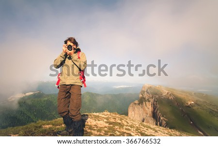 Man Traveler with photo camera and backpack hiking outdoor Travel Lifestyle survival concept mountains clouds on background  - stock photo