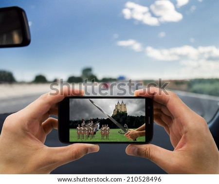 man traveling by car and seeing on your smartphone a medieval movie - stock photo