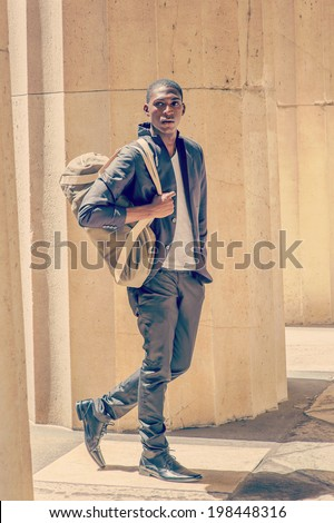 Man Traveling. Carrying a shoulder bag, a young black college student is walking though columns on campus, confidently looking forward. Street Fashion.  - stock photo