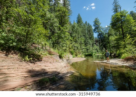 Man trekking through Oak Creek Canyon on the West Fork trail in Arizona, between Flagstaff and Sedona surrounded by beautiful red rock and lush green forest - stock photo