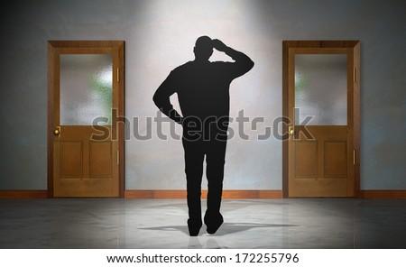 Man Trying to Decide Between Two Doors - stock photo