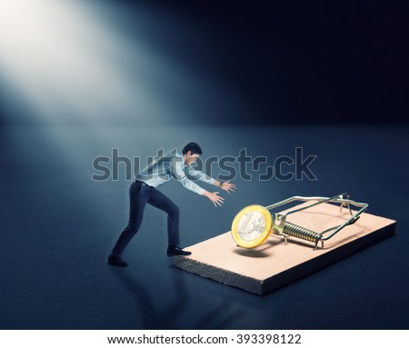 Man trying to pick a gold coin - stock photo