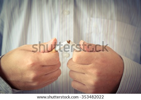 Man trying to quit smoking by breaking a cigarette. Conceptual image. Close-up. Vintage look - stock photo