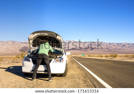 Man trying to repair his car in the desert - stock photo